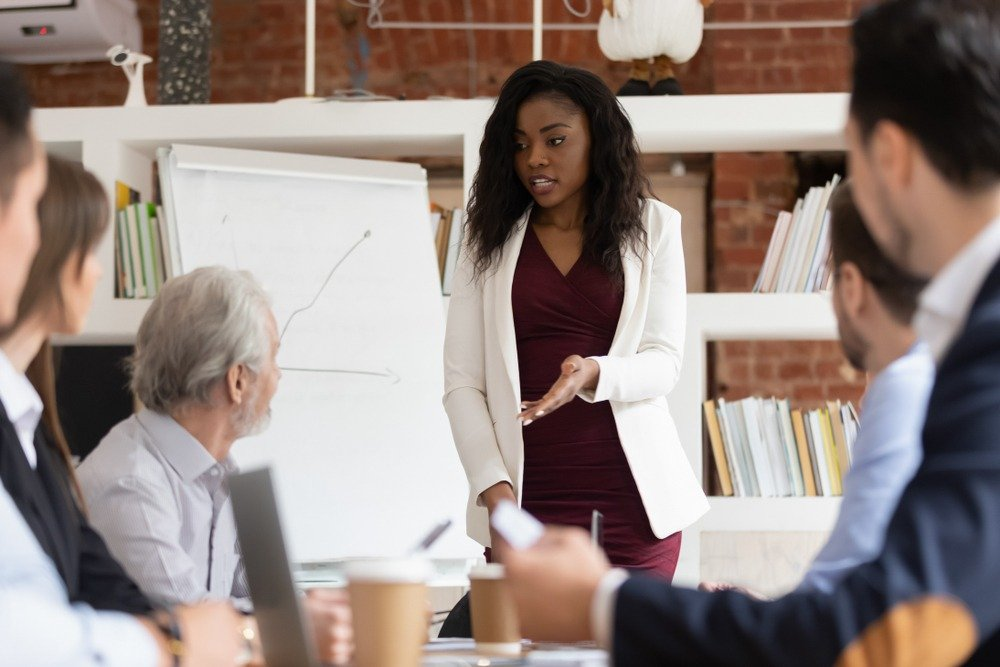 Presentation skills: Image of a female leader standing in front of a chart, training her team