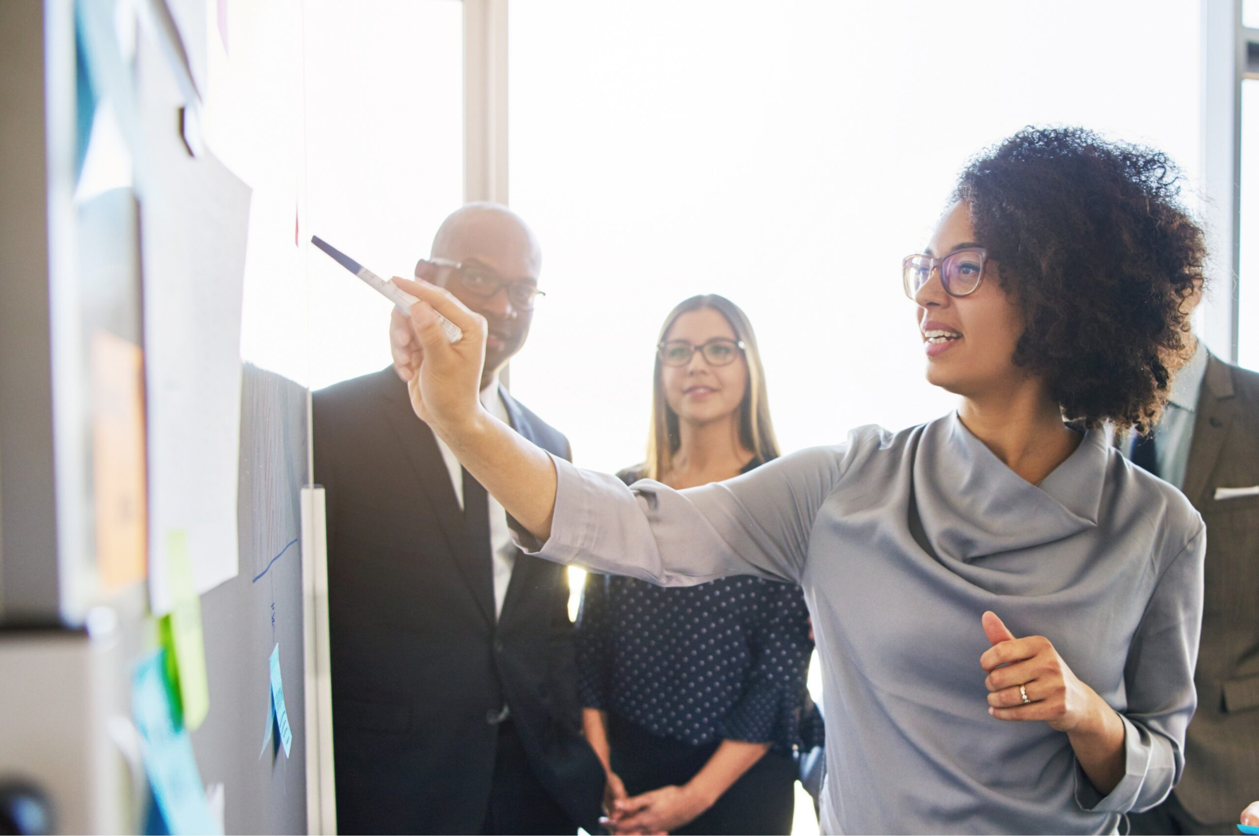 Emotional intelligence: Image of a female executive pointing with a pen at sticky notes leading a discussion with three other colleagues