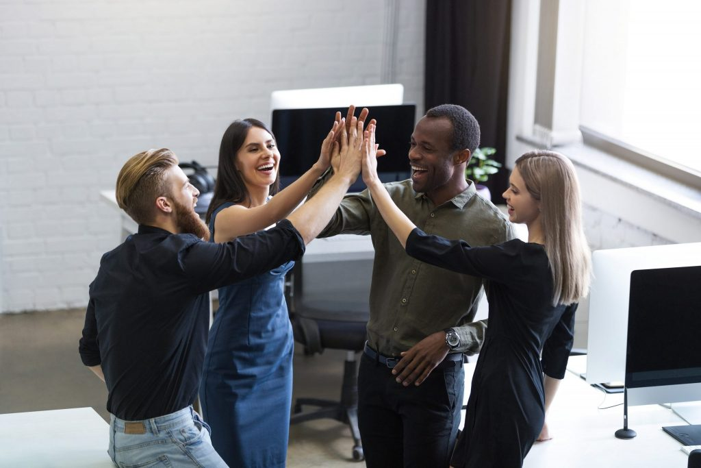 Diversity and inclusion: Image of a team high fiving each other, indicating that the leader has earned their trust and inspired their contribution.