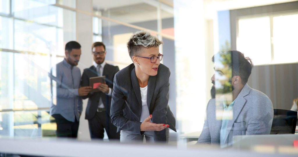 Emotional intelligence why it can matter more than IQ: Image of a female executive confident, in control and comfortable leading men