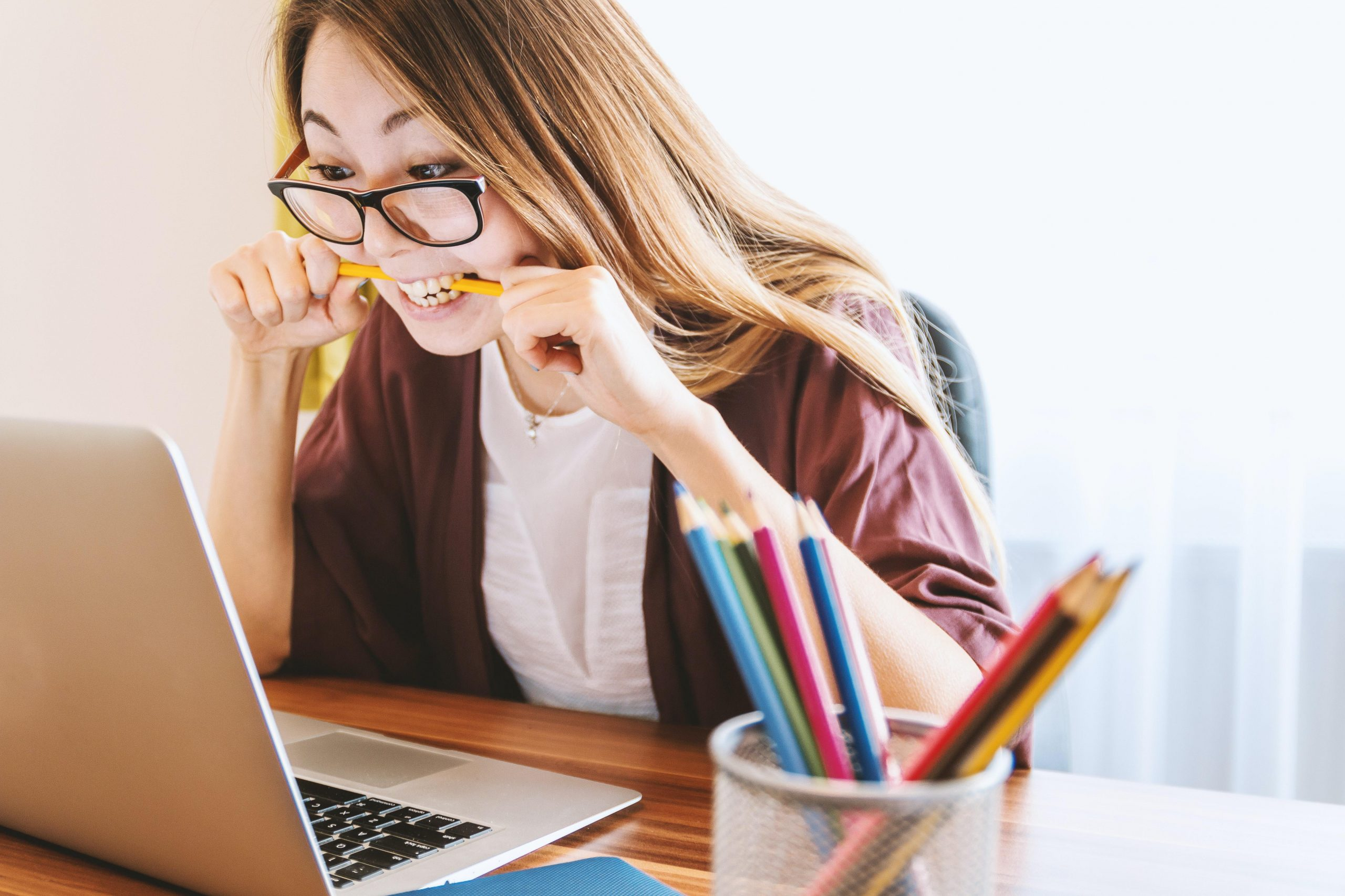 Feeling Overwhelmed: Image of a woman sitting at her computer biting a pencil
