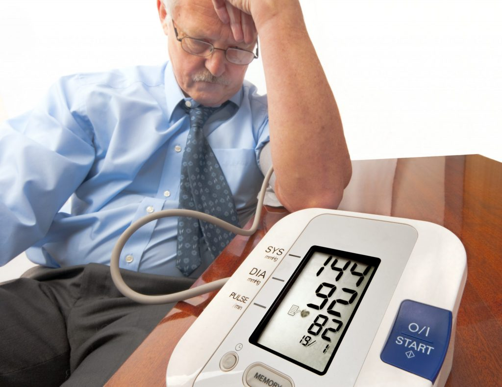 Health problems: Image of a man slouching sitting in a chair with his head in his hands having his blood pressure taken