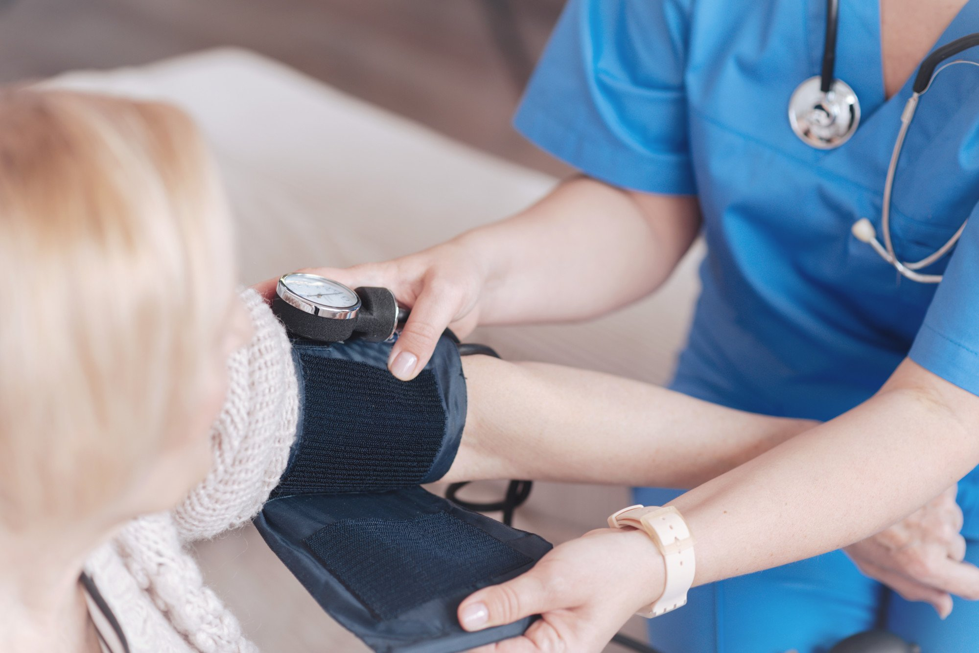 Stress management: Image of a woman having her blood pressure taken by a nurse