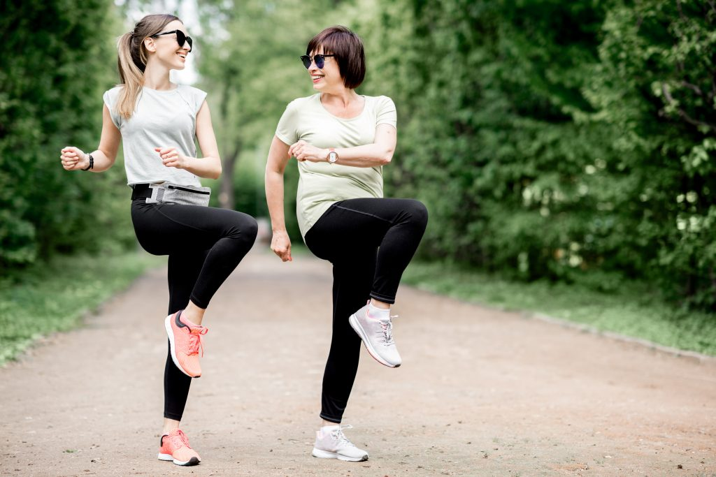 Aerobic exercise: Image of a mother and daughter outdoors doing aerobics