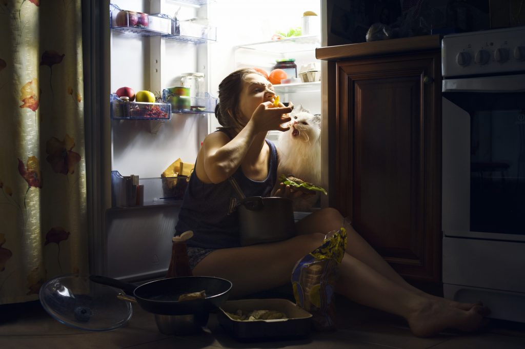 Bad habits: Image of a woman in the dark sitting in front of her refrigerator putting food in her mouth