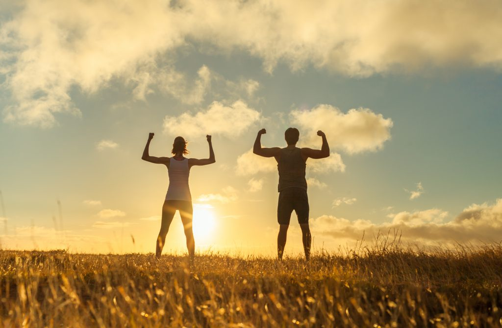 Celebration: Image of a man and woman outdoors with their arms up celebrating their fitness