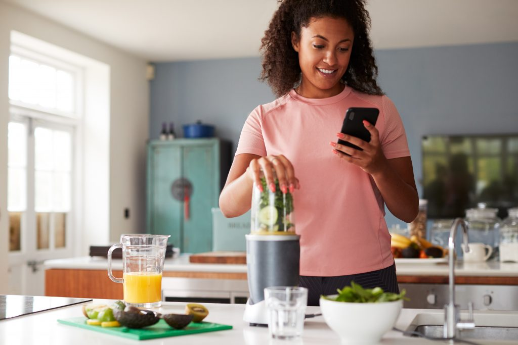 Good habits: Image of a woman standing at her kitchen counter making a healthy smoothie while looking at her phone