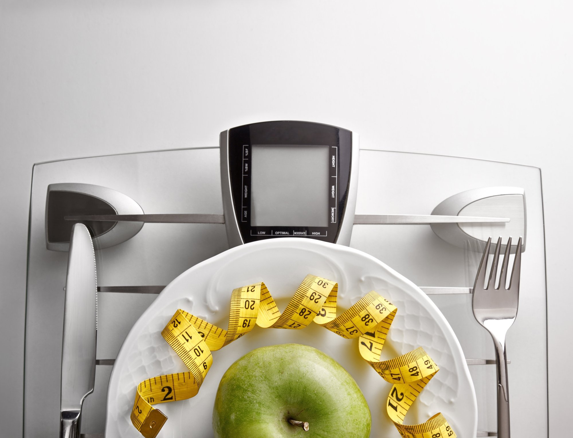 image of a plate holding an apple and measuring tape on top of a scale that has a knife and fork.