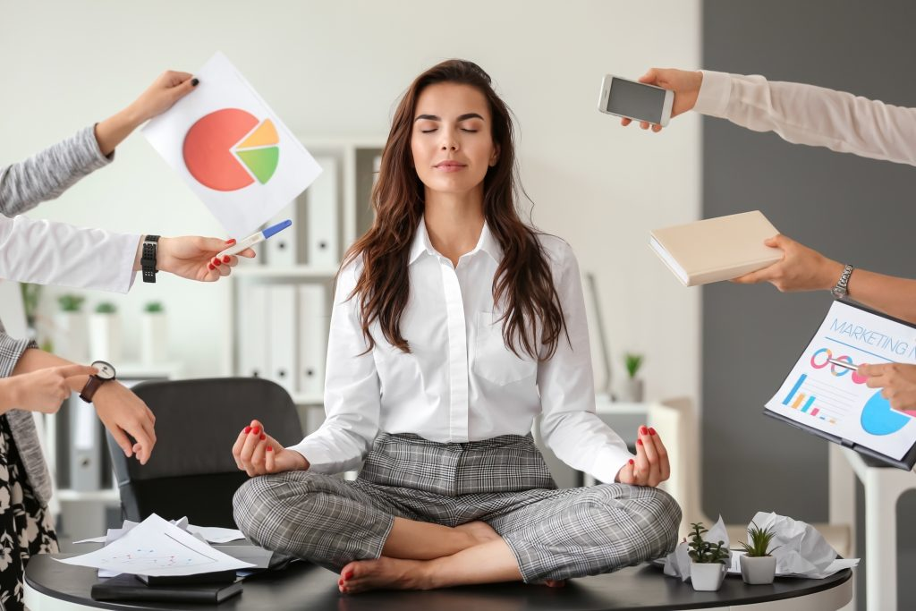 Visualization: image of a woman sitting on her desk meditating while ignoring the chaos of her workplace